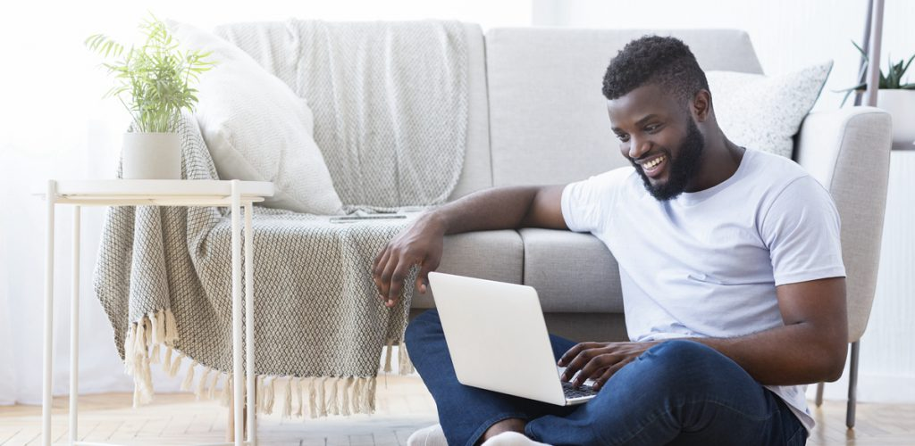 African guy playing video game on laptop computer, sitting on floor at home, free space