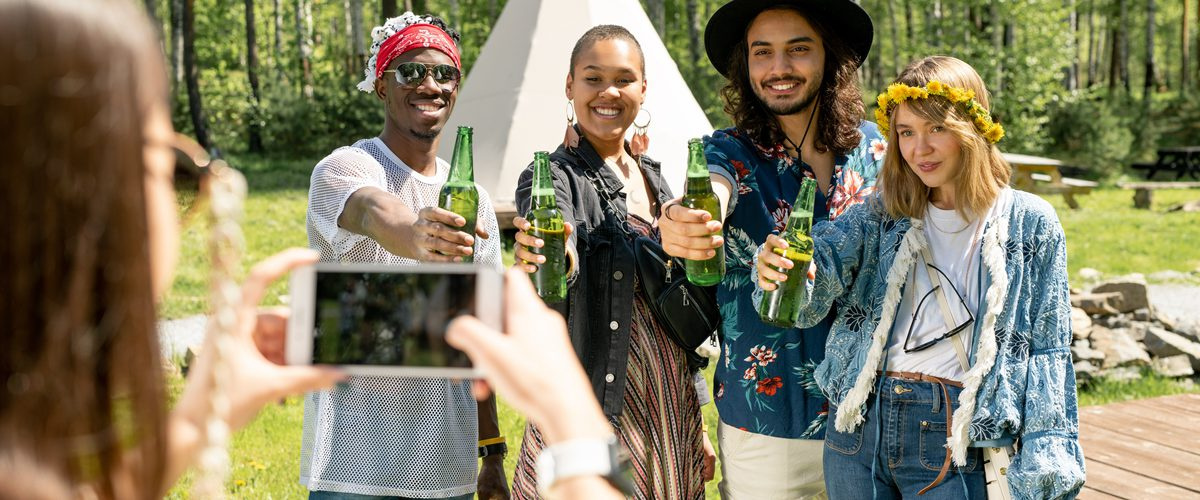 Group of positive young multi-ethnic people in hippie outfits posing with beer bottles for photo at countryside festival