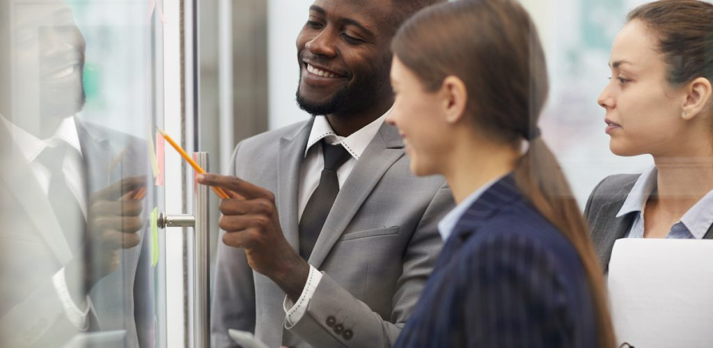 Side view at multi-ethnic group of business people planning startup project placing sticky notes on glass wall, copy space