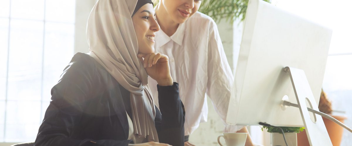Discussion with colleague. Beautiful arabian businesswoman wearing hijab while working at openspace or office. Concept of occupation, freedom in business area, leadership, success, modern solution.