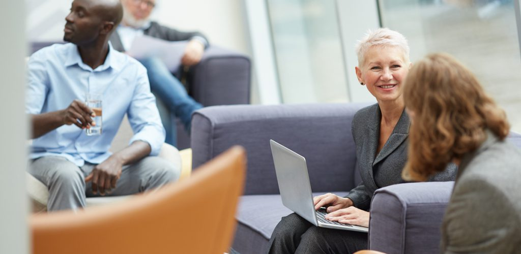 Portrait of successful senior businesswoman smiling cheerfully while talking to colleagues and using laptop during meeting in office hall, copy space